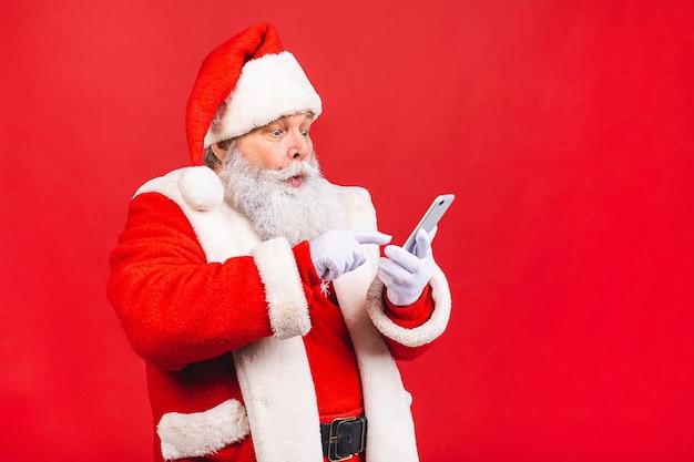 Alter mann im weihnachtsmannkostüm, das auf einem mobiltelefon lokalisiert auf rot hält Premium Fotos
