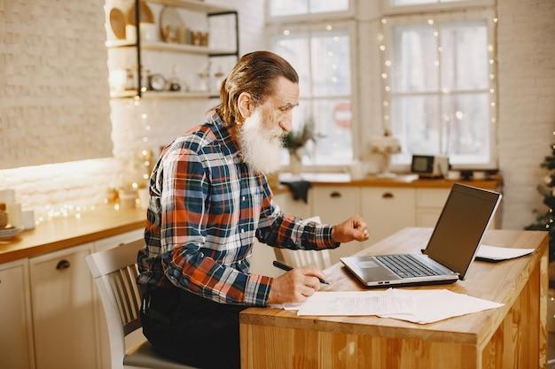 Alter mann mit laptop. großvater sitzt in einer weihnachtsdekoration. mann in einem zellenhemd. Kostenlose Fotos