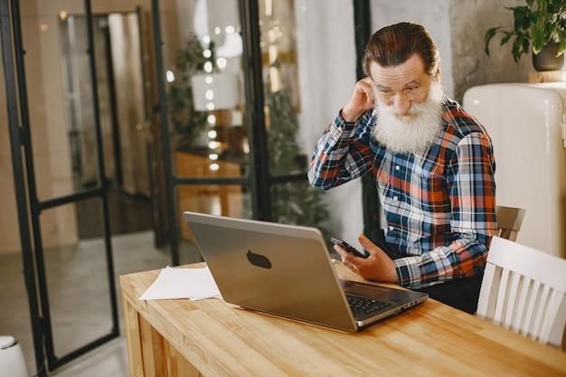 Alter mann mit laptop. großvater sitzt in einer weihnachtsdekoration. mann mit handy. Kostenlose Fotos