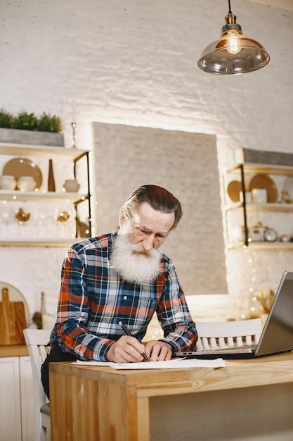 Alter mann mit laptop. großvater sitzt in einer weihnachtsdekoration. Kostenlose Fotos