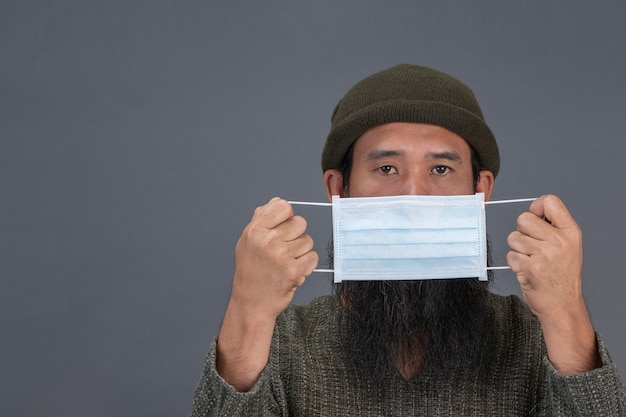Alter mann trägt maske, während auf schwarzer wand stehend. Kostenlose Fotos