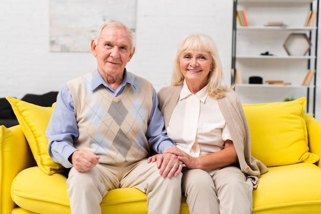 Alter mann und frau, die auf gelbem sofa sitzt Kostenlose Fotos
