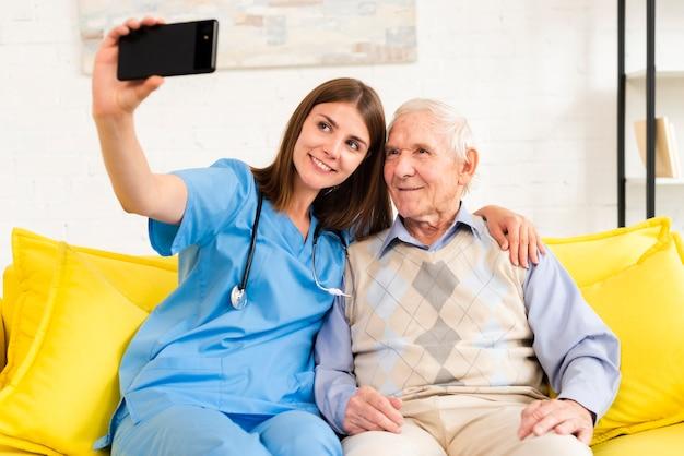 Alter mann und krankenschwester, die ein selfie nehmen Kostenlose Fotos
