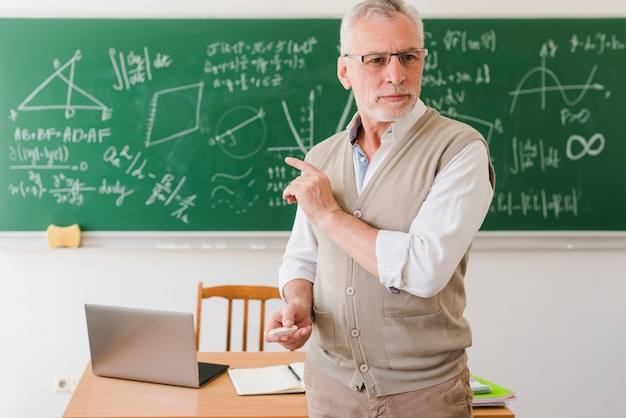 Alter professor, der im klassenzimmer darstellt Kostenlose Fotos