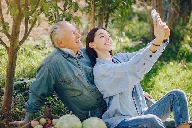 Alter senior, der in einem sommergarten mit ernte steht Kostenlose Fotos