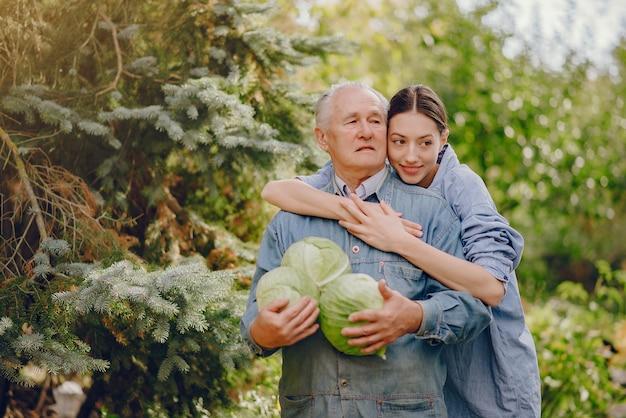 Alter senior, der in einem sommergarten mit kohl steht Kostenlose Fotos