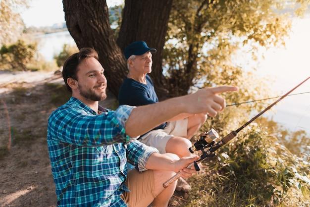 Alter und junger mann angeln mit angelruten. Premium Fotos