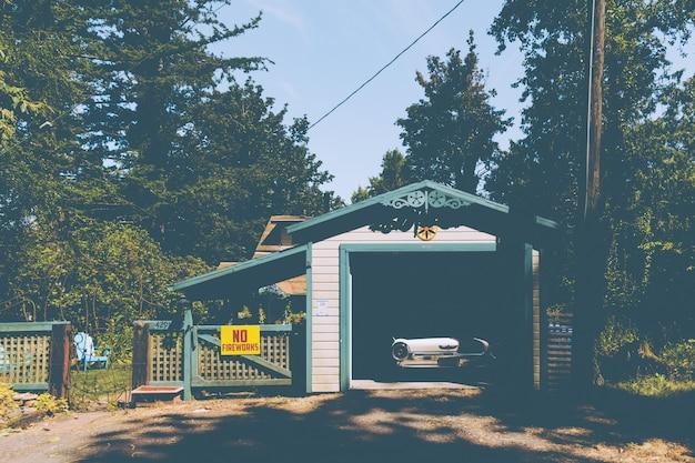 Altes altes auto, das in einer kleinen garage neben einem schild an einem zaun geparkt wird Kostenlose Fotos
