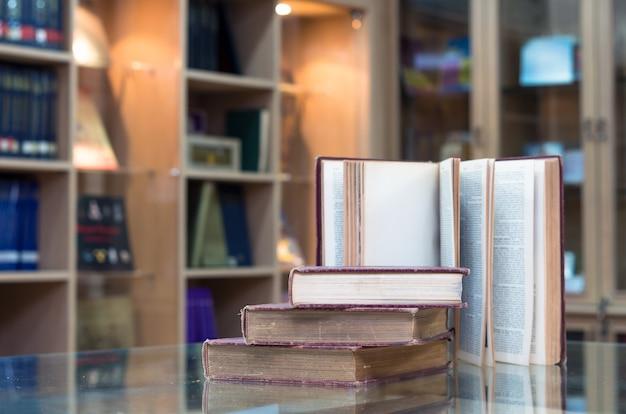 Altes buch auf dem glas schreibtisch in der bibliothek Premium Fotos