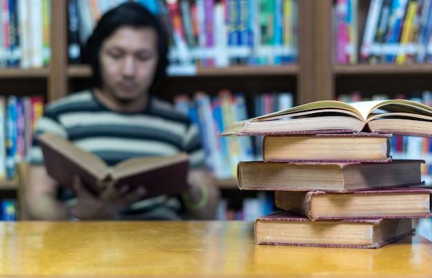 Altes buch auf dem schreibtisch in der bibliothek mit dem mann, der den buchhintergrund liest Premium Fotos