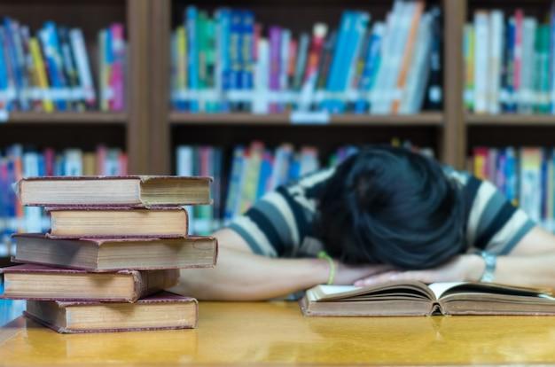 Altes buch auf dem schreibtisch in der bibliothek mit dem mann, der über dem buchhintergrund schläft Premium Fotos