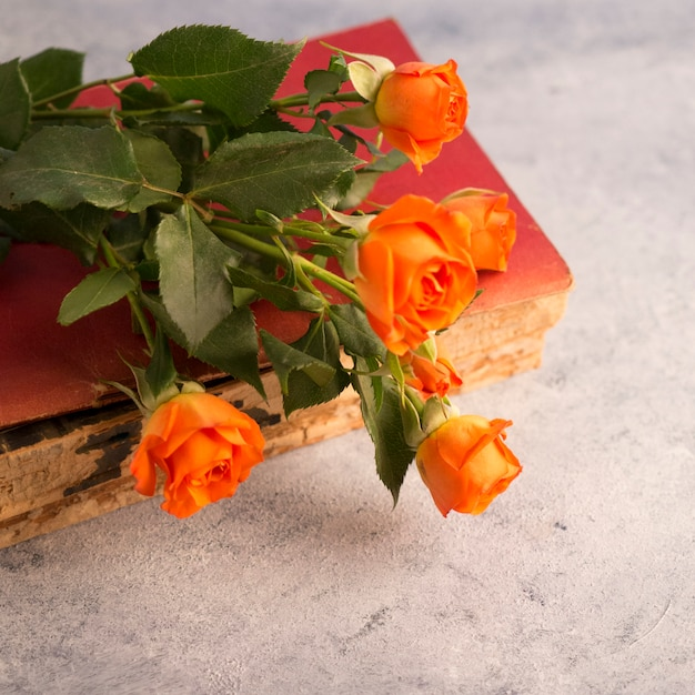Altes buch und blumenblumenstrauß auf schäbiger oberfläche Kostenlose Fotos