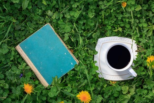Altes buch und eine schale heißer kaffee auf einer draufsicht des grünen wiesensommers oder des frühlingsmorgens Premium Fotos