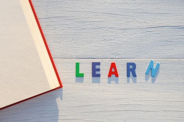 Altes buch und lernen bunte alphabet wort. draufsicht auf weißen hölzernen hintergrund Premium Fotos