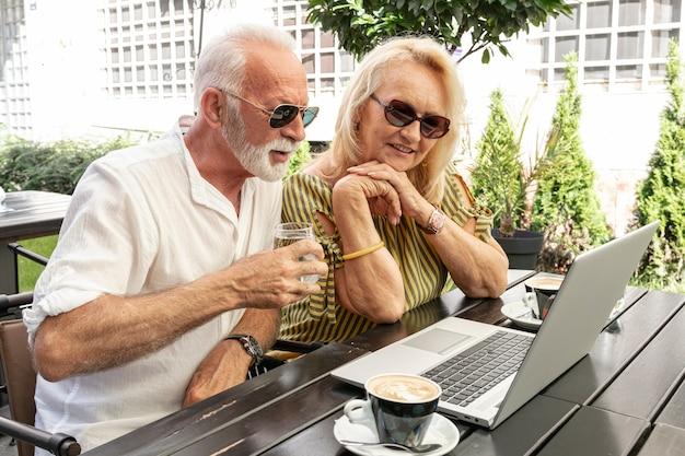 Altes ehepaar, das einen laptop betrachtet Kostenlose Fotos