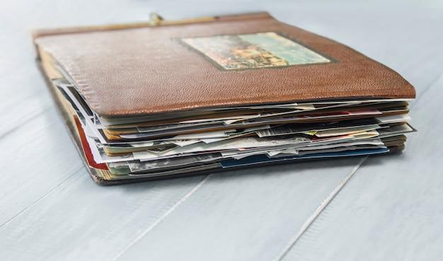 Altes fotoalbum mit fotos auf einem holztisch. Premium Fotos
