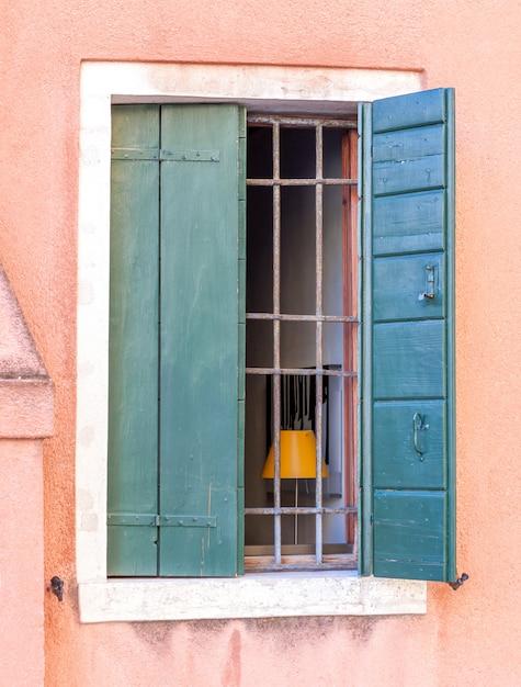 Altes gitterfenster mit hölzernen fensterläden Premium Fotos