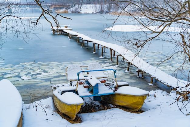 Altes katamaran im winter auf der schneeküste des gefrorenen flusses nahe bei der langen brücke. Premium Fotos