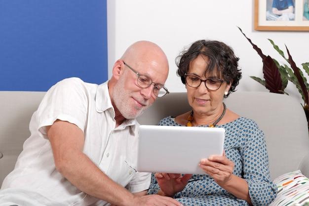 Altes paar mit einem tablet und lächelnd Premium Fotos