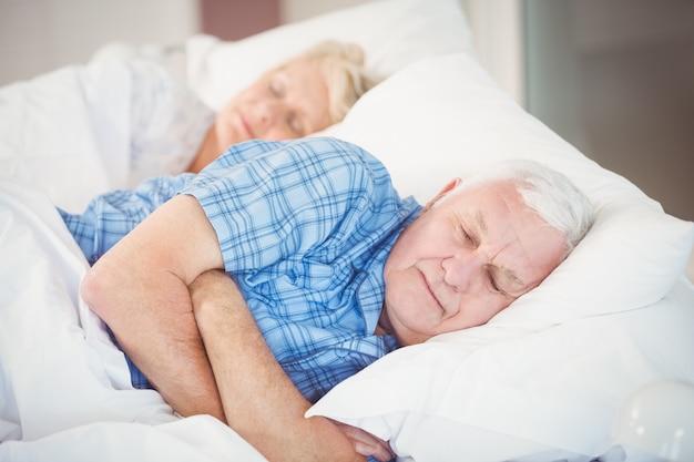 Altes paar schläft auf dem bett Premium Fotos