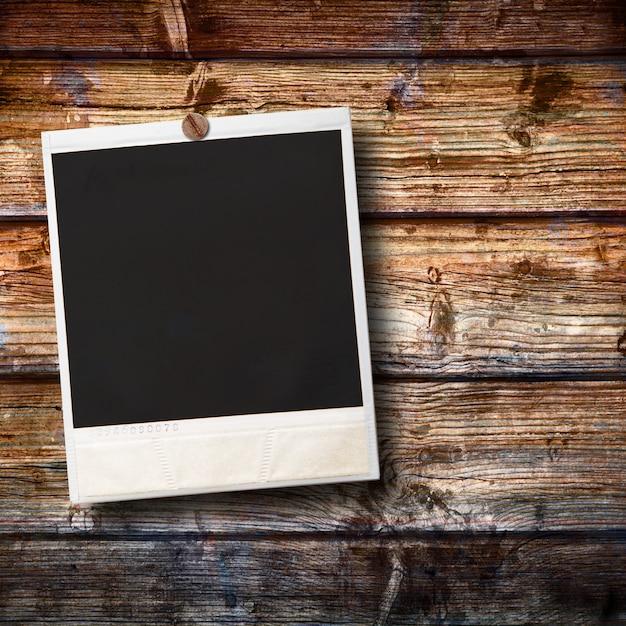 Altes polaroid, das am holz hängt Premium Fotos