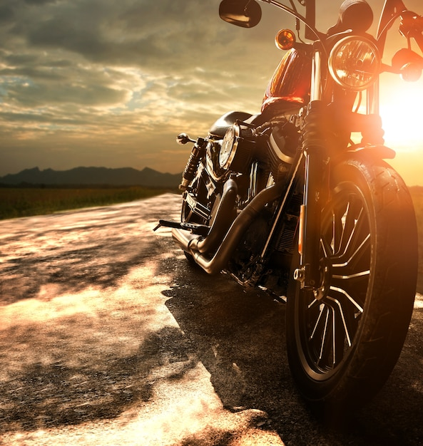 Altes retro- motorrad, das auf landstraße gegen schönes licht des sonnenunterganghimmels reist Premium Fotos