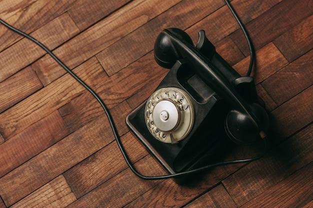 Altes schwarzes telefon auf dem boden Premium Fotos