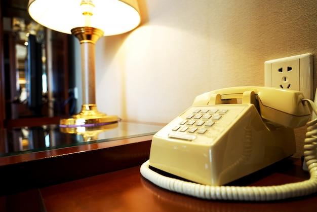 Altes telefon auf holztisch nahe wand und rampe im hotelzimmer Premium Fotos