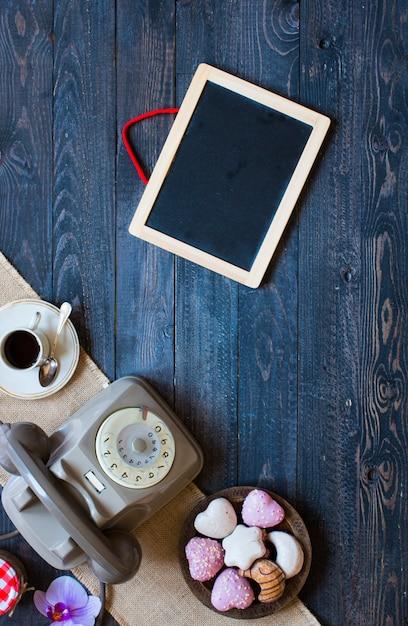 Altes weinlesetelefon, mit biscotti, kaffee, schaumgummiringe auf einem hölzernen hintergrund Premium Fotos