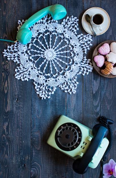 Altes weinlesetelefon mit biscottikaffeeschaumgummiringen auf einem hölzernen hintergrund Premium Fotos