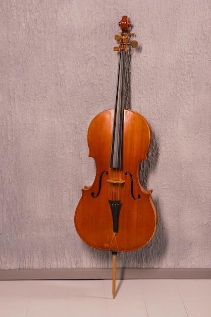 Altes zerschlagenes cello, das nahe einer grauen strukturierten wand steht. Premium Fotos