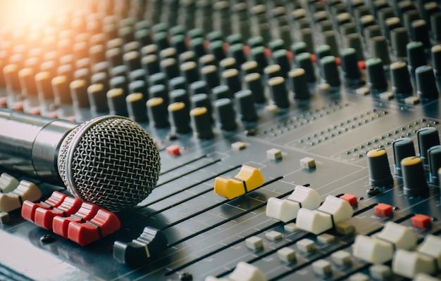 Am audiomixer sind drahtlose mikrofone angebracht, um die nutzung der öffentlichkeitsarbeit im besprechungsraum zu steuern. Premium Fotos