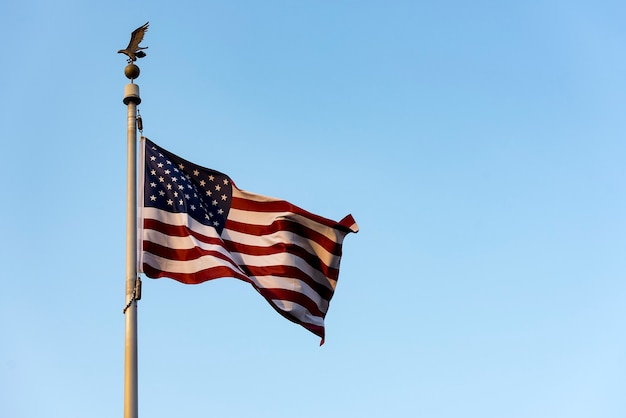 Amerikanische flagge, die gegen blauen himmel, usa-fahnenschwingen wellenartig bewegt Premium Fotos
