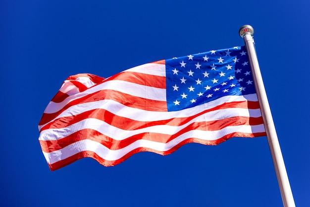 Amerikanische flagge gegen blauen himmel im wind Premium Fotos