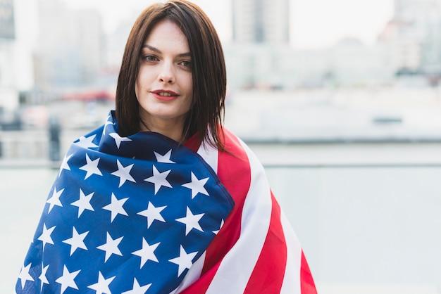 Amerikanische frau eingewickelt in der flagge am unabhängigkeitstag Kostenlose Fotos