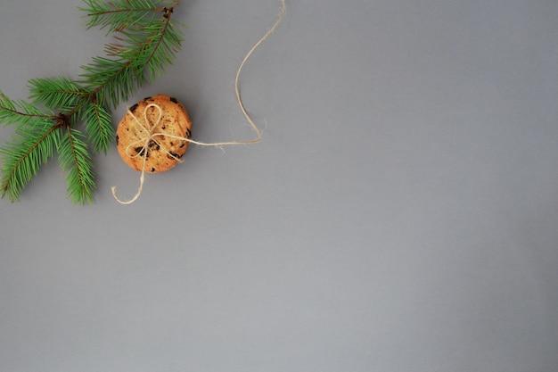 Amerikanische weihnachtsplätzchen und grüner tannenzweig auf grau Premium Fotos