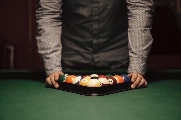 Amerikanischer billard poule. dreieck der billardkugeln. ein mann, der sich bereit macht, ein billardspiel zu beginnen. Premium Fotos