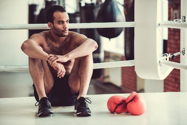 Amerikanischer boxer mit dem bloßen torso schaut weg. Premium Fotos