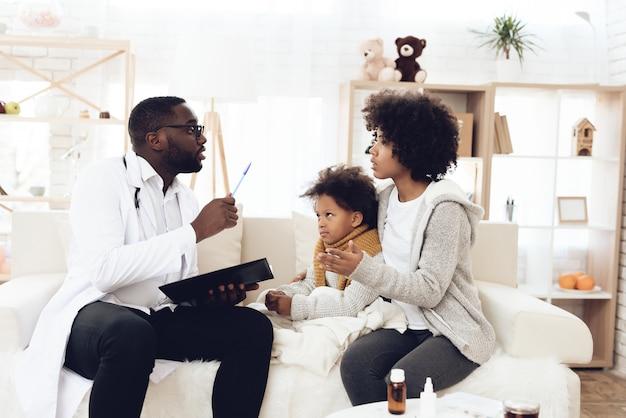 Amerikanischer doktor, der mutter mit krankem kind erklärt. Premium Fotos