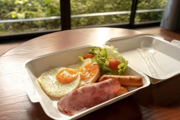 Amerikanischer frühstücksmahlzeitstil in einem papierkastensatz. kleine mahlzeit aus schinken und spiegeleiern. Premium Fotos
