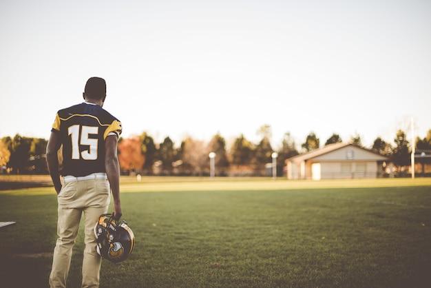 Amerikanischer fußballspieler, der im feld steht und sich auf das spiel vorbereitet Kostenlose Fotos