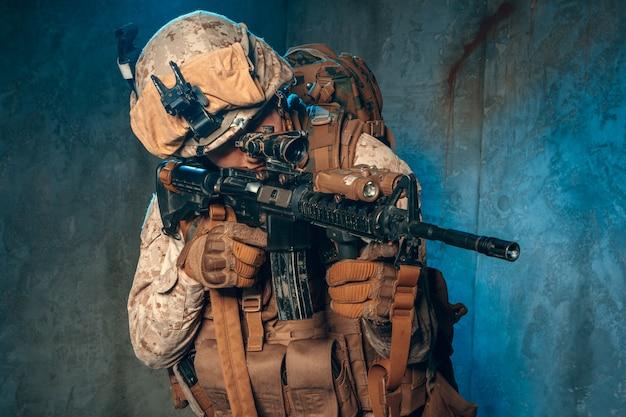 Amerikanischer privater militärunternehmer, der ein gewehr schießt. studioaufnahme Premium Fotos