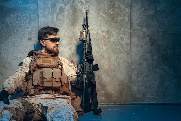 Amerikanischer privater militärunternehmer, der gewehr hält. bild auf einem dunklen hintergrund Premium Fotos