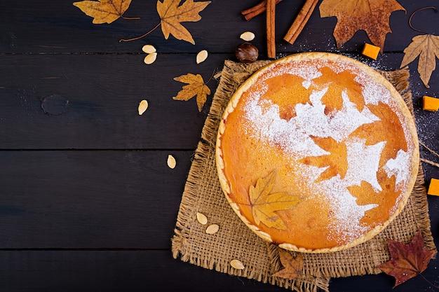 Amerikanischer selbst gemachter kürbiskuchen mit zimt und muskatnuss, kürbiskernen und herbstlaub auf einem holztisch. thanksgiving-essen. ansicht von oben. flach liegen Premium Fotos