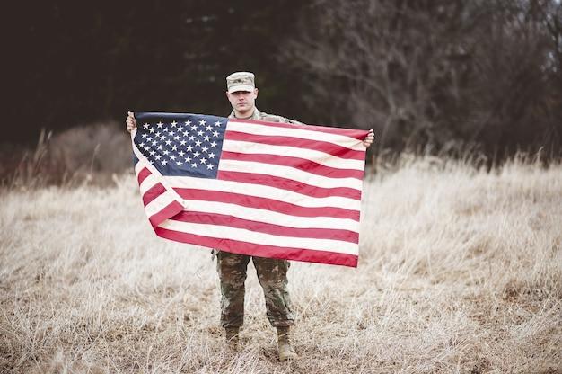 Amerikanischer soldat, der die amerikanische flagge hält Kostenlose Fotos