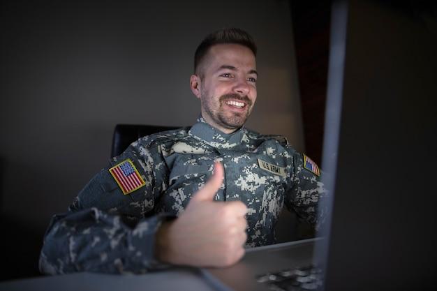 Amerikanischer soldat in militäruniform, der daumen vor dem computer hält Kostenlose Fotos