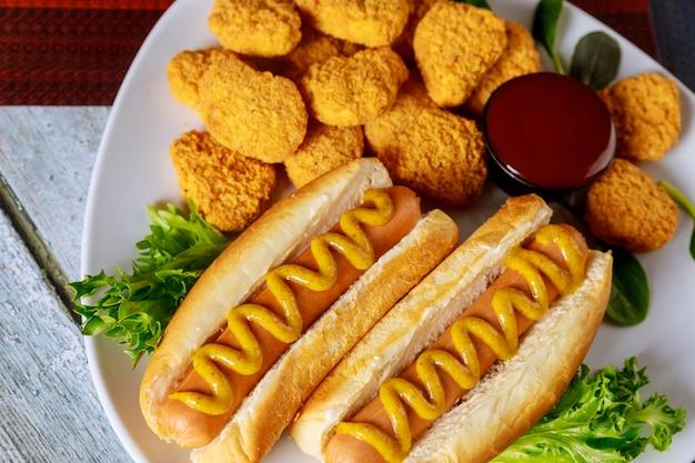 Amerikanisches fast food. hot dogs und hühnernuggets mit sauce. Premium Fotos