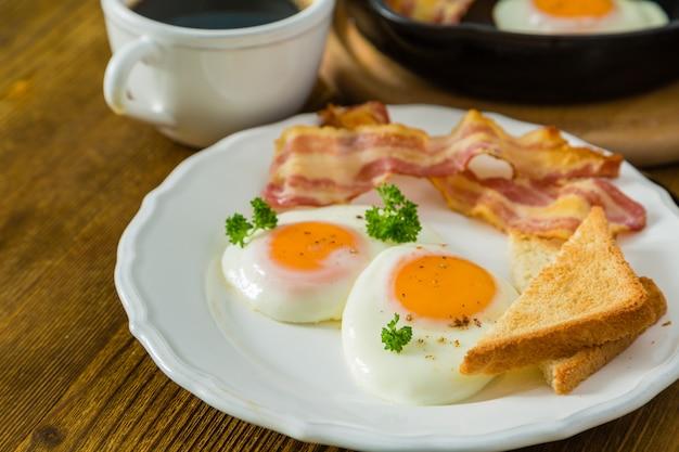Amerikanisches frühstück mit spiegeleiern, speck, toast, pfannkuchen, kaffee und saft Premium Fotos