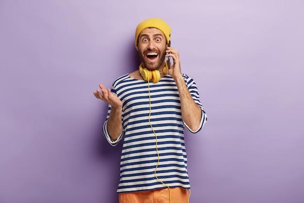 Amüsiert freudiger hipster hält handy in der nähe von ohr, hat lustige telefongespräche, trägt gelben hut und gestreiften pullover Kostenlose Fotos