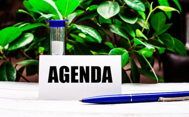 An der wand aus grünen blättern der pflanze steht ein stift auf dem tisch, eine sanduhr und eine karte mit der aufschrift agenda Premium Fotos